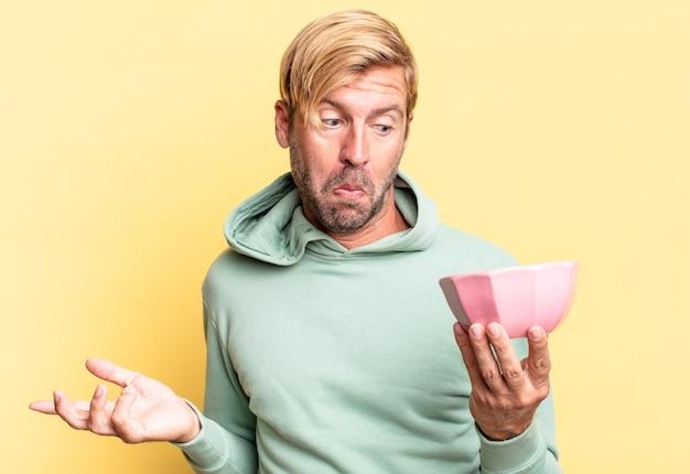 Блондинка красивый взрослый мужчина держит пустой горшок у желтой стены