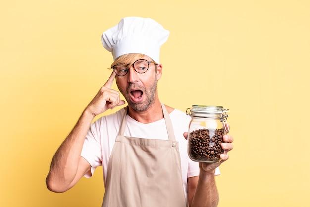 커피 콩 병을 들고 금발 잘 생긴 요리사 성인 남자
