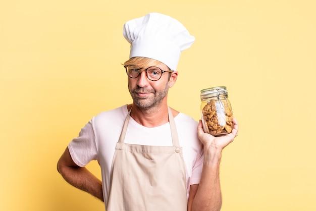 自家製のクッキーボトルを保持している金髪のハンサムなシェフの大人の男