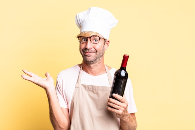 Blonde handsome chef  adult man holding a bottle of wine