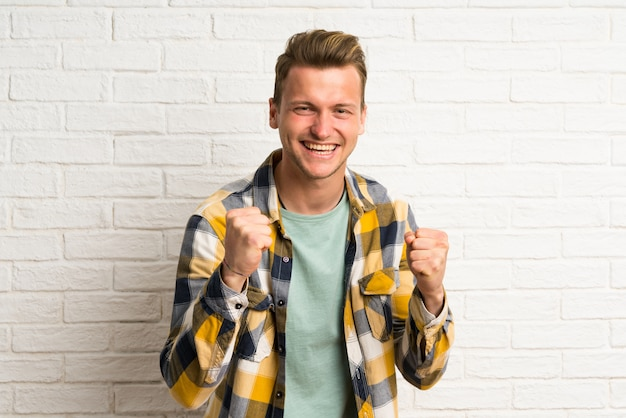 Blonde handsome man celebrating a victory