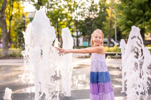 Blonde happy child girl in long purple dress running between water flow in city summer park.