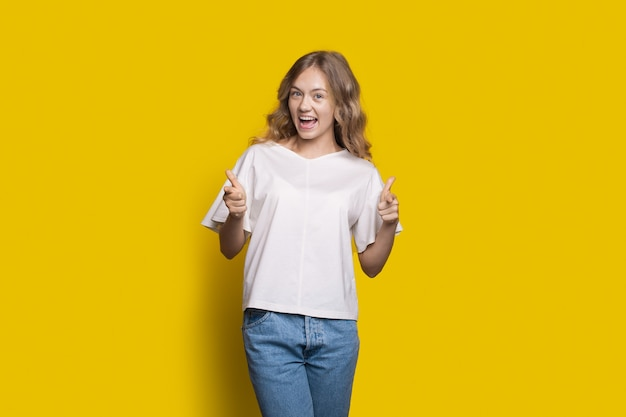 Blonde happy girl is pointing with opened mouth smiling on a yellow wall