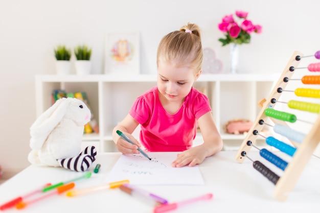 Белокурый счастливый чертеж маленькой девочки siitting белой таблицей в светлой комнате с деревянными красочными абакусом. дошкольное образование, раннее обучение