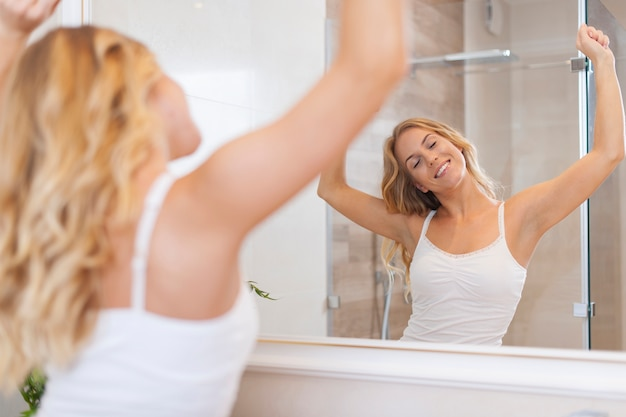 Blonde happy woman stretching in morning