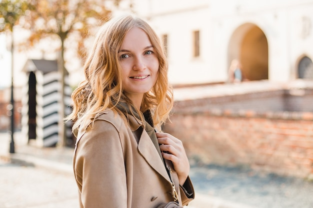 通りを歩いている金髪の幸せな女性