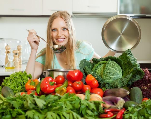新鮮な野菜を使ったブロンドの主婦の料理