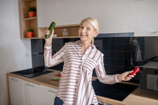 キッチンで楽しんで、喜びを感じている金髪の主婦