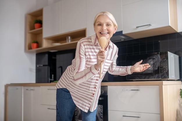 キッチンで楽しんで笑っている金髪主婦
