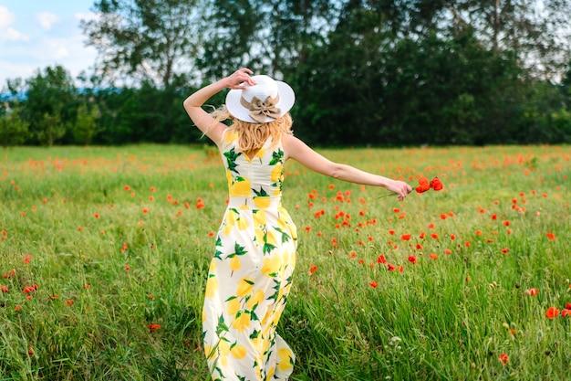 드레스와 모자를 쓴 금발이 기쁨으로 양귀비 밭을 가로질러 달린다