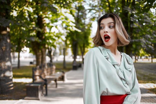 公園の屋外の新鮮な空気の赤いスカートで金髪。高品質の写真