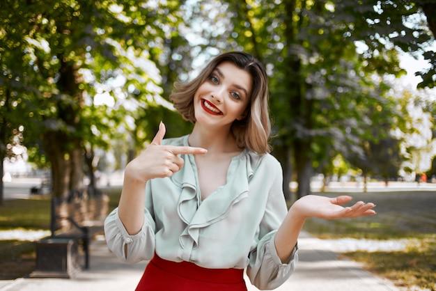 公園の屋外の新鮮な空気の赤いスカートで金髪