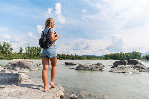 岩の上の川のそばに立っている黒いバックパックと美しいデニムのショートパンツで金髪。女の子の旅行者の後ろからの肖像画。写真旅行のコンセプト。純粋な自然を楽しむ