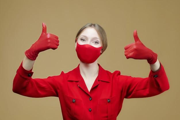 赤い手袋とマスクのブロンドは親指を立てます。コロナウイルス感染を防ぐという概念19。