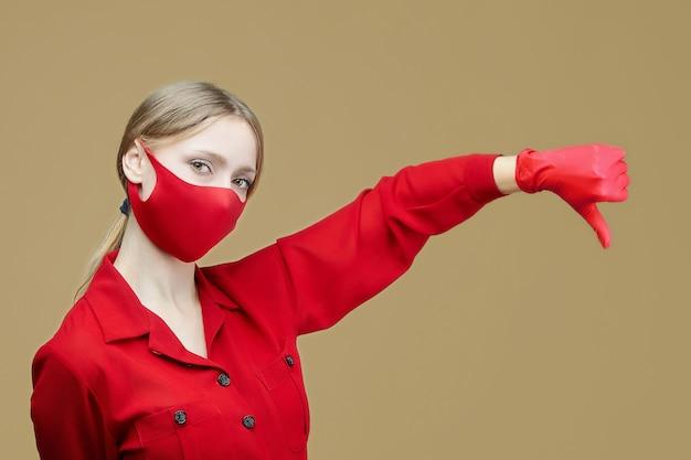 赤い手袋とマスクを身に着けた金髪は彼女の親指を下に向けます。コロナウイルス感染を防ぐという概念19。