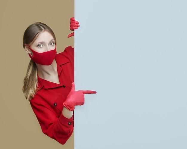 赤い手袋とマスクのブロンドは、大きな空白の看板でポーズをとります。