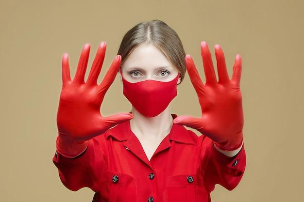 赤い手袋とマスクを身に着けた金髪は、彼女の手でstopのサインを示しています。コロナウイルス感染を防ぐという概念19。