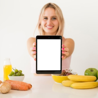 Blonde influencer showing blank tablet
