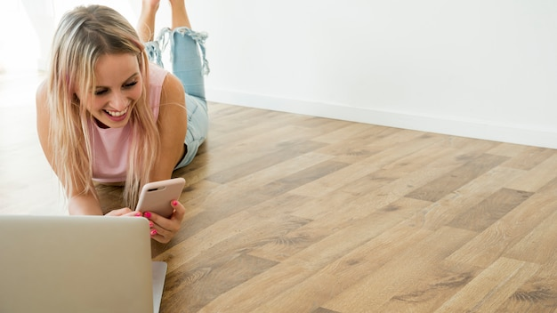 Blonde influencer using smartphone on the floor