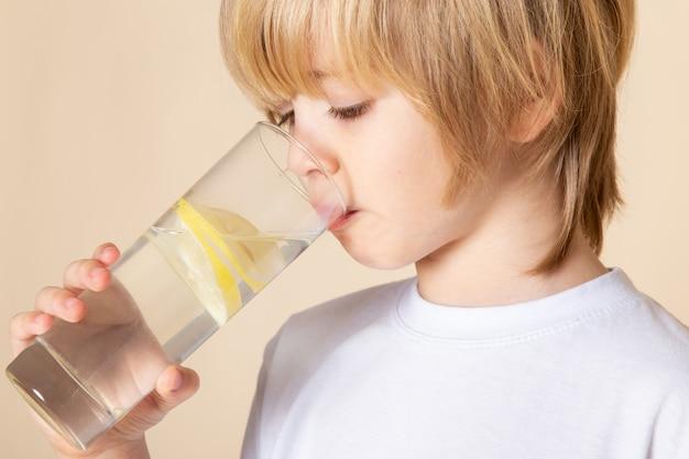 Blonde kid little cute drinking lemon juice on pink wall