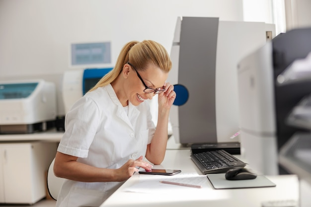 실험실에 앉아서 휴식 시간에 스마트 폰을 사용하는 멸균 제복을 입은 금발 실험실 조교