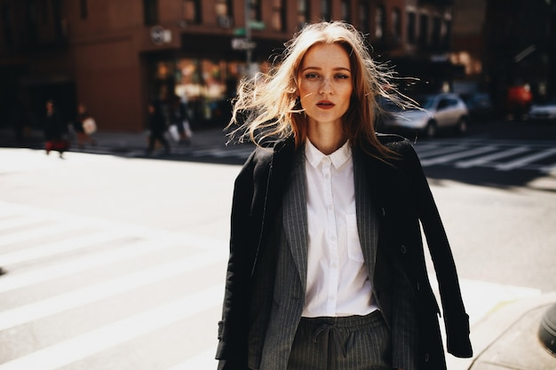 Blonde lady in black coat stands on the sunny street somewhere in new york city