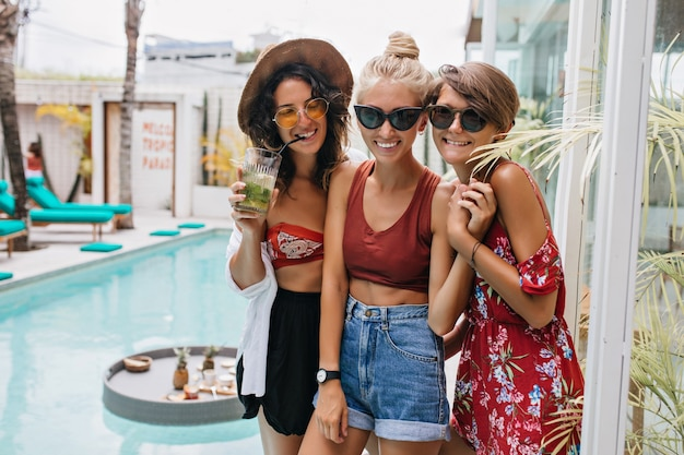 Blonde lady in black sunglasses chilling with best friends at resort. outdoor photo of tanned women having fun in pool.