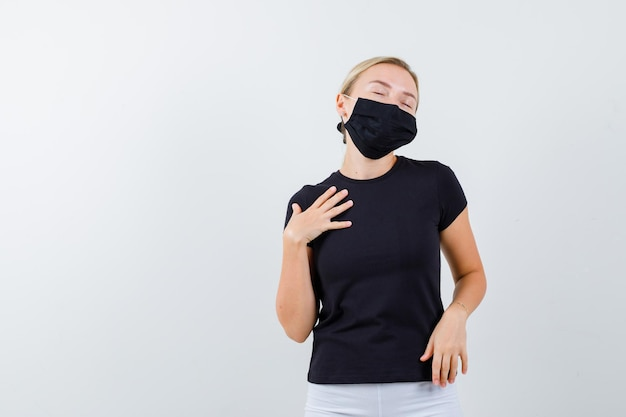 Blonde lady in black t-shirt, black mask holding hand on chest isolated