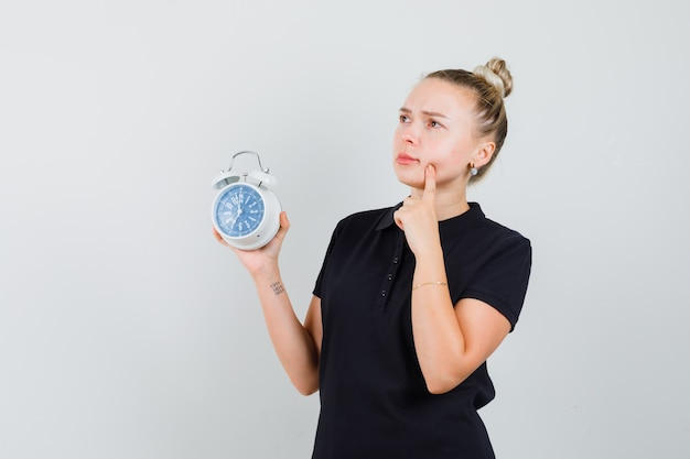 Blonde lady in black t-shirt holding alarm clock and looking thoughtful , front view.
