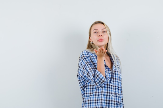 Blonde lady blowing air kiss with pouted lips in checked shir