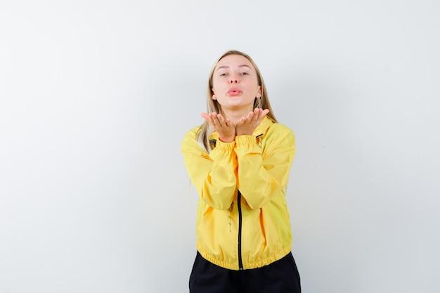 トラックスーツで口をとがらせた唇で空気のキスを吹いて、かわいく見えるブロンドの女性。正面図。