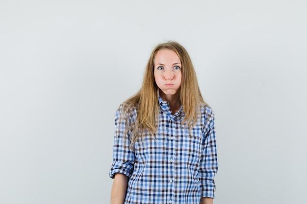 금발 아가씨 셔츠에 뺨을 불고 긍정적 인 찾고.
