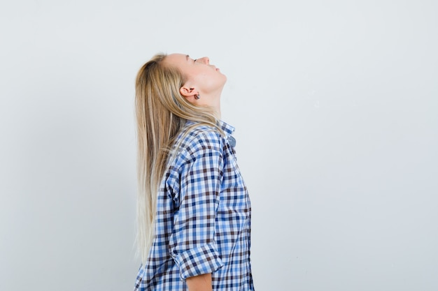 Blonde lady in casual shirt bending head back and looking peaceful .