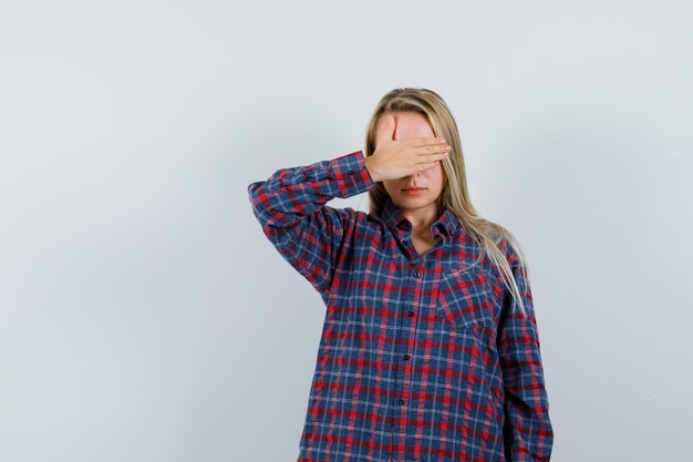 Signora bionda in camicia casual tenendo la mano sugli occhi e guardando triste, vista frontale.