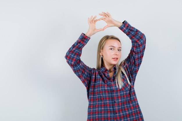 Signora bionda in camicia casual che mostra il gesto del cuore e che sembra felice, vista frontale.