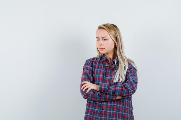 Signora bionda in camicia casual in piedi con le braccia incrociate e guardando triste, vista frontale.
