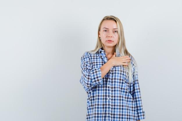 Signora bionda in camicia a quadri tenendo la mano sul cuore e guardando fiducioso