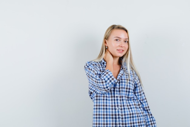 Blonde lady in checked shirt posing with hand on neck and looking pretty
