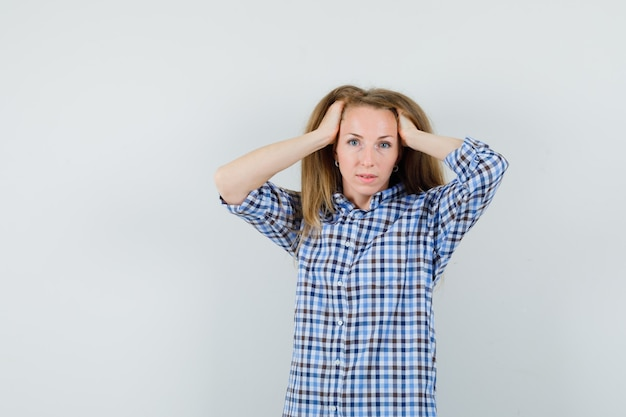 Blonde lady clasping head in hands in shirt and looking charming ,