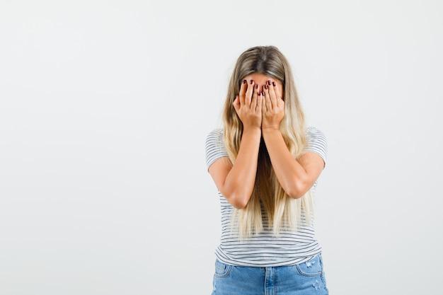 Tシャツを着た手で顔を覆い、悲しそうに見える金髪の女性。正面図。