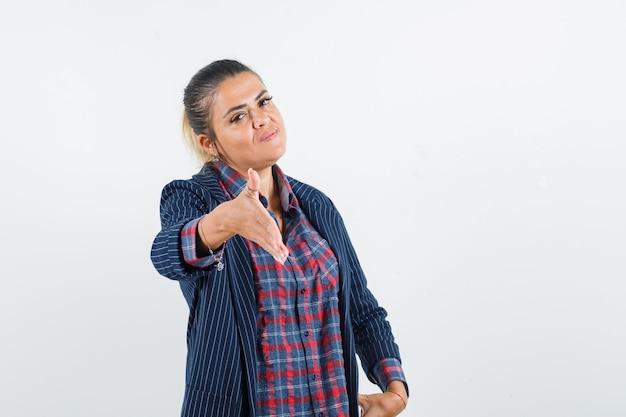 Signora bionda che dà la mano per tremare in camicia, giacca e sembra gentile, vista frontale.