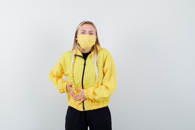 운동복, 마스크에 고통스러운 맹장염이 있고 몸이 좋지 않은 금발 아가씨.