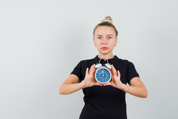 Blonde lady holding alarm clock in black t-shirt and looking concerned , front view.