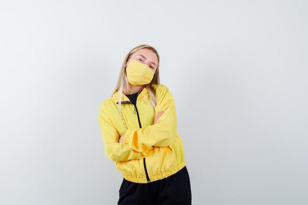 Signora bionda che tiene le braccia incrociate in tuta da ginnastica, maschera e guardando fiducioso, vista frontale.