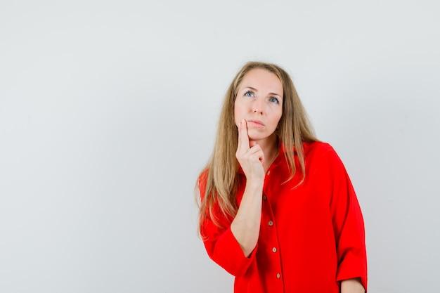 Signora bionda che tiene il dito sul mento in camicia rossa e guardando pensieroso.