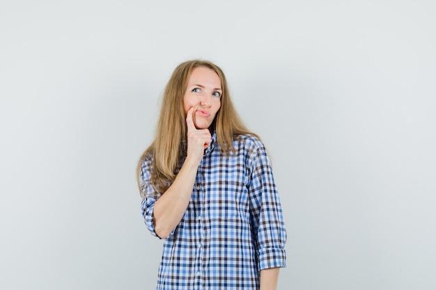 셔츠에 입 근처에 손가락을 잡고 주저하는 금발 아가씨,