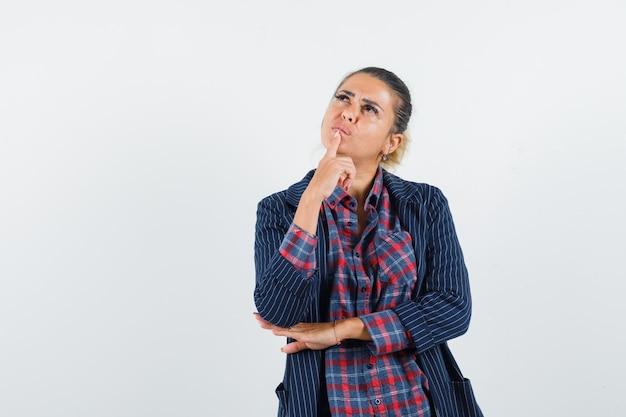 シャツ、ジャケット、夢のような、正面図で顎に指を保持しているブロンドの女性。
