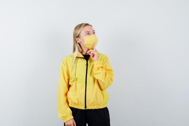 トラックスーツ、マスク、物思いにふけるあごに指を保持しているブロンドの女性。正面図。