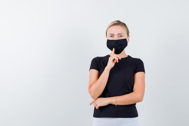 고립 된 검은 티셔츠에 그녀의 의료 마스크에 손가락을 잡고 금발 아가씨