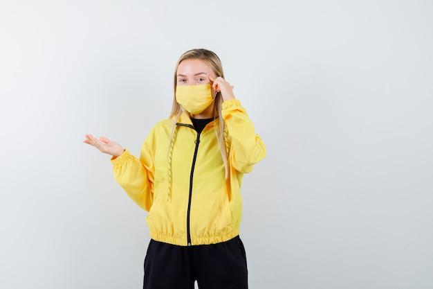 こめかみに指を持ち、トラックスーツ、マスク、賢明な正面図で手のひらを広げている金髪の女性。